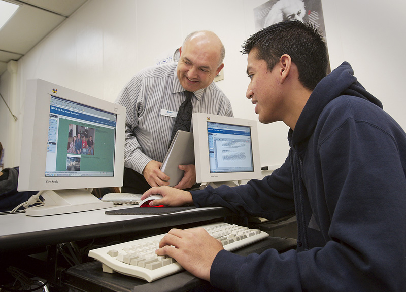 A teacher oversees a student working on a computer