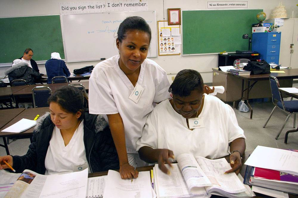 An instructor assists two students studying