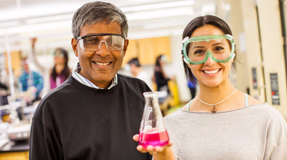 a chemistry professor and student hold a flask