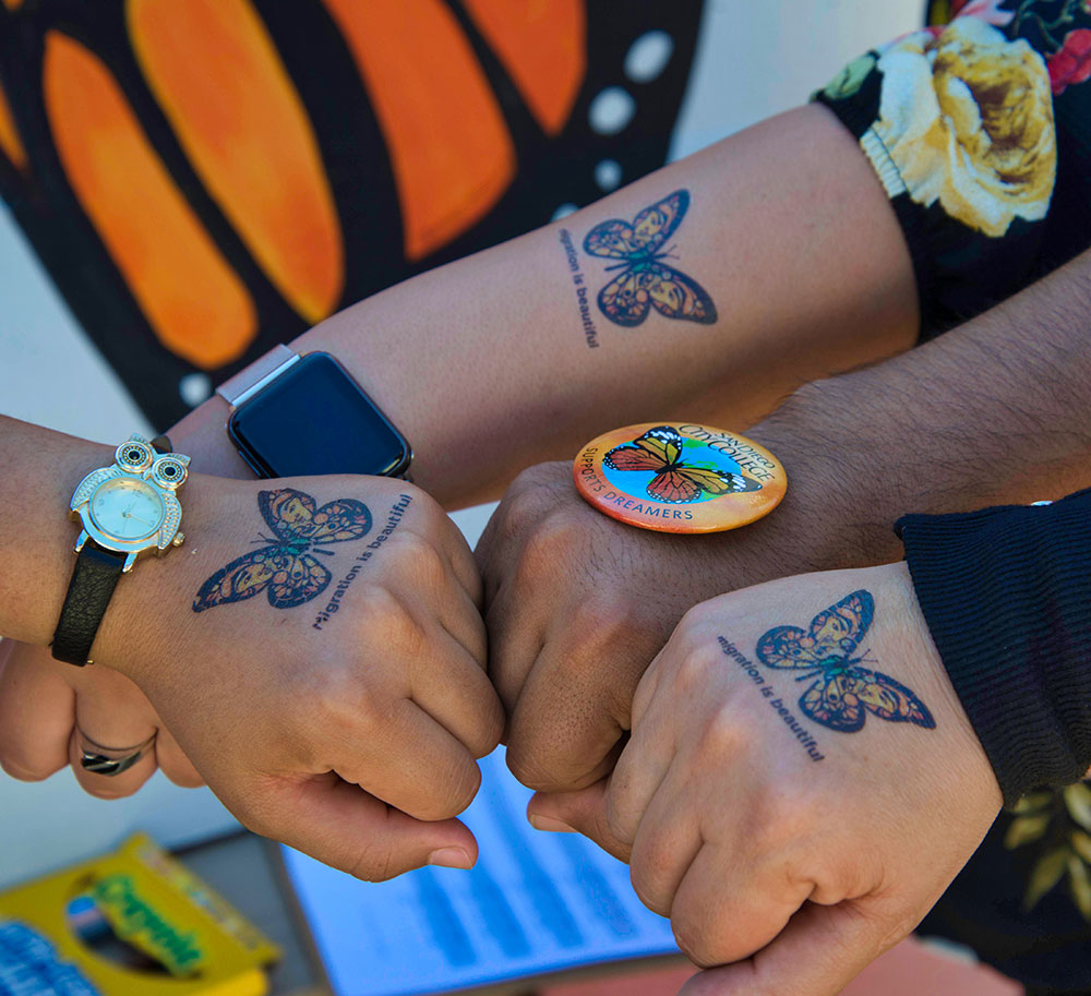 Butterflies tattooed on hands represent support for dreamers