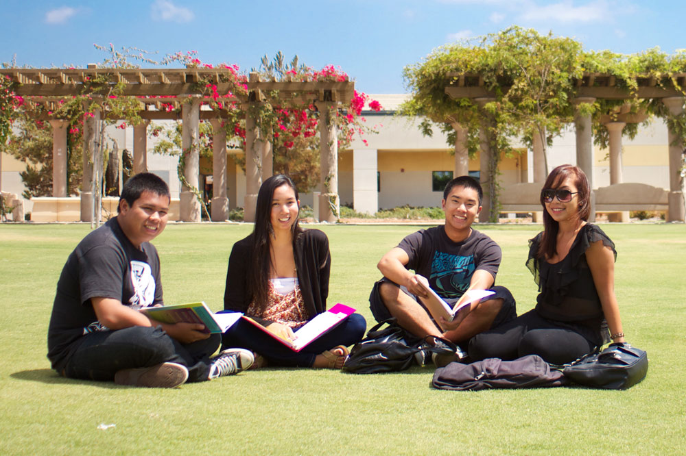 four students sit on the lawn