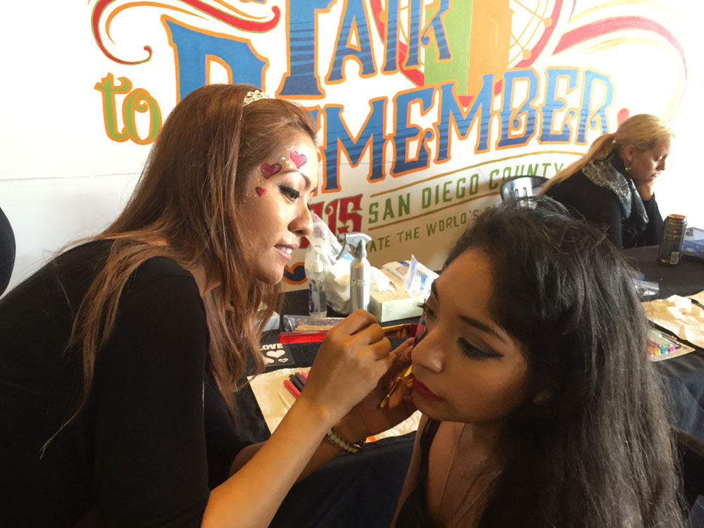 A cosmetology student puts face paint on a woman at the San Diego County Fair in 2015