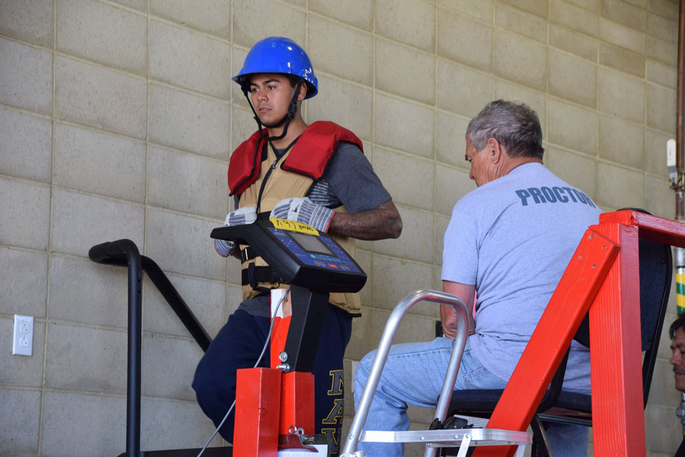 A firefighter in training climbs a stair machine while wearing 75 pounds as part of a training test