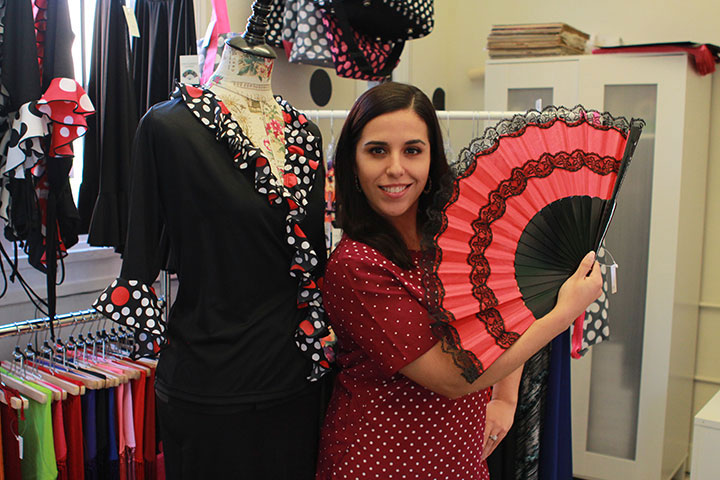 María del Mar Hinojosa poses with a flamenco dress and fan in her store The Pure Flamenco.
