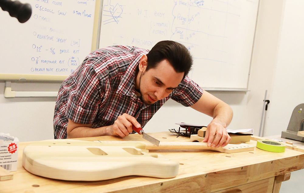 A City College Manufacturing Engineering Technology student builds an electric guitar.