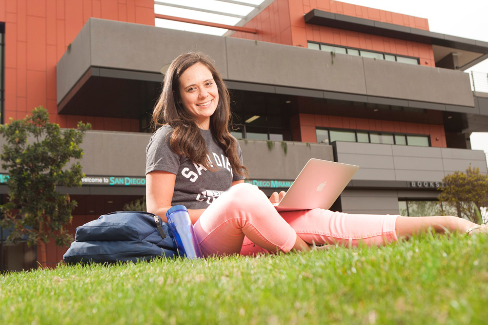 A student sits on the grass with her laptop at Miramar College