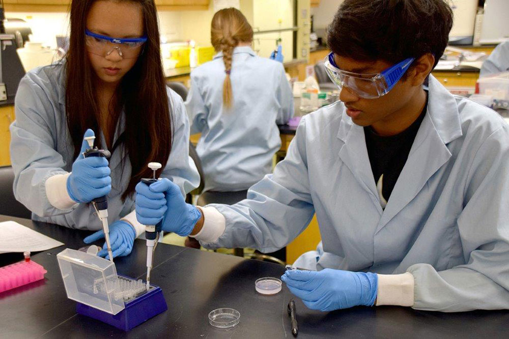 Two students use syringes to fill vials in a science lab.