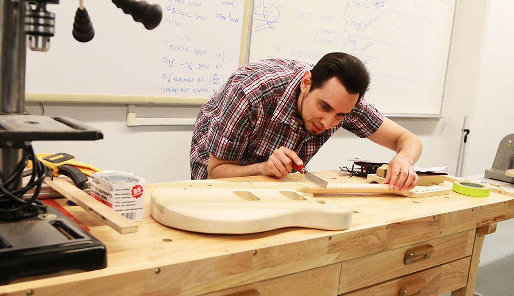 A City College student at a work bench shaping a guitar