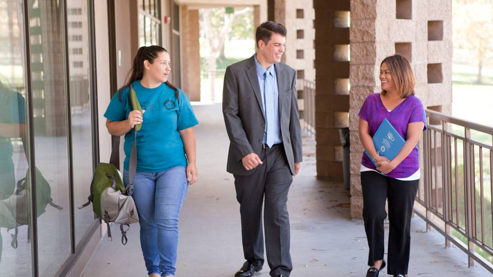 President Carlos O. Turner Cortez walks with two students at Continuing Education
