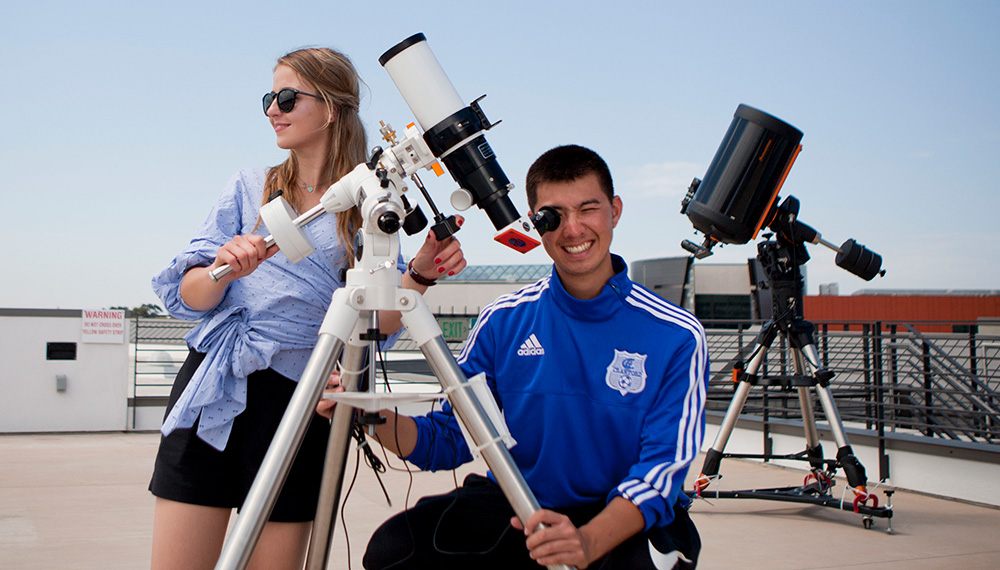 Miramar College students using a solar telescope on the roof of the college's Science Building.