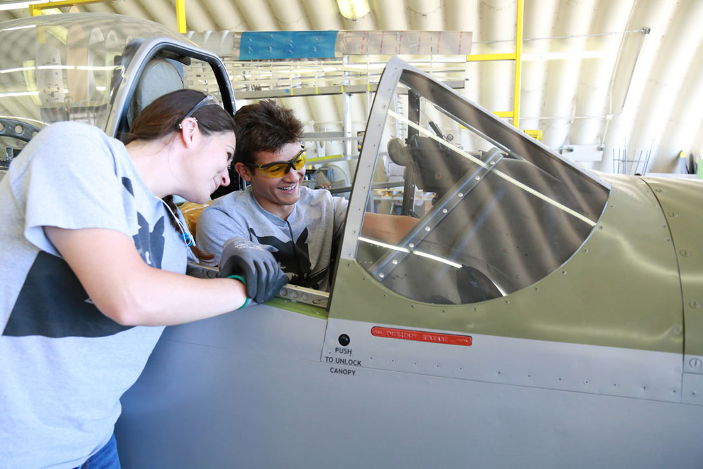 Miramar College aviation maintenance technology students Genevieve Cindrich and Derrick Caceres assist with restoration of a P-51 Mustang.