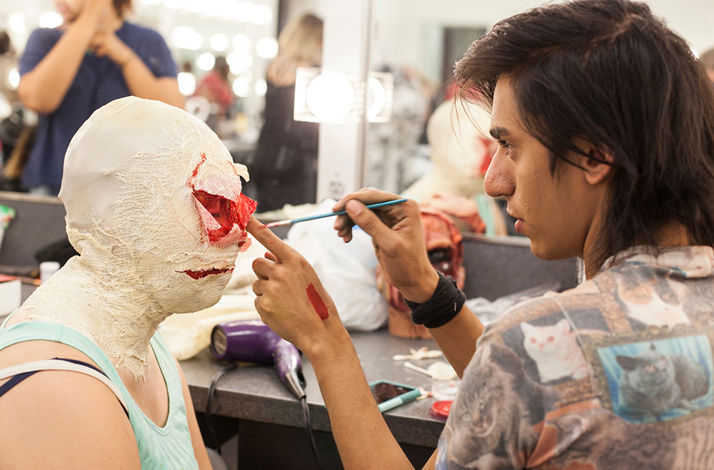 A student paints fake blood on someone's face in a special effects makeup class at San Diego City College.