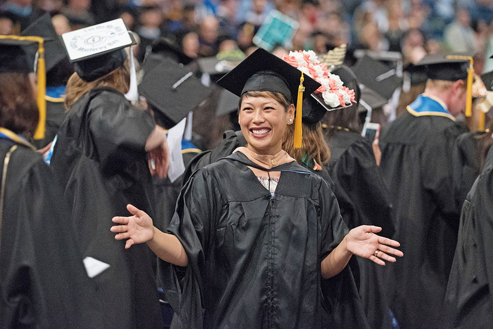 Mesa College employee in a cap and gown at graduation.