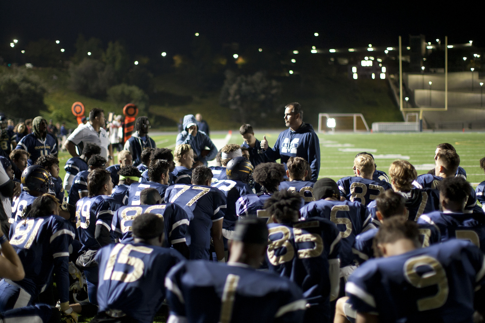 Mesa College football coach talks to the team on the field