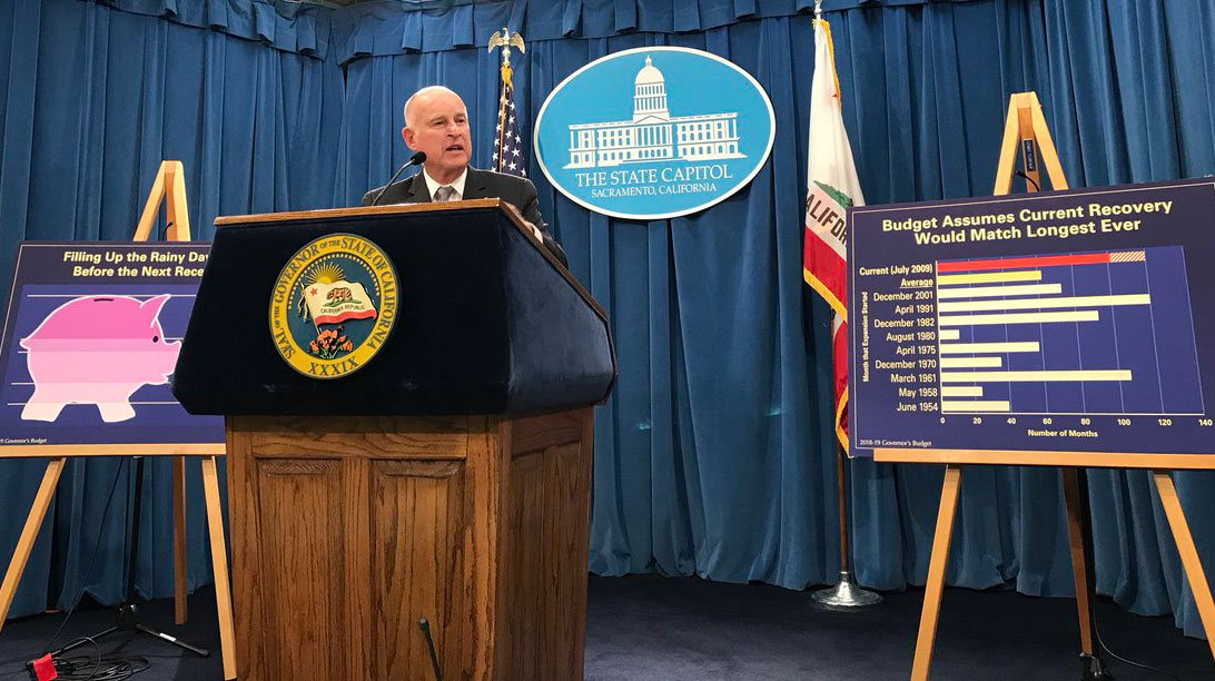 Governor Jerry Brown stands at a podium at a budget press conference