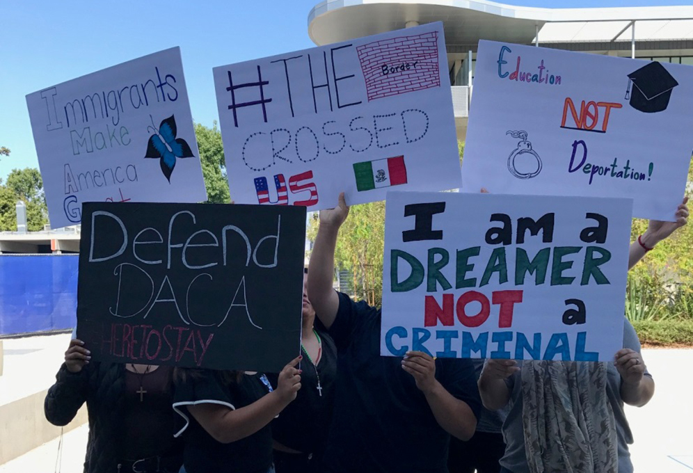 DACA supporters hold protest signs