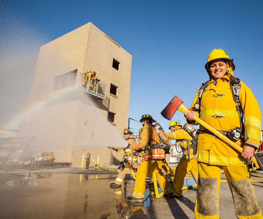 A fire cadet holds and ax and an another cadet sprays a firehose.