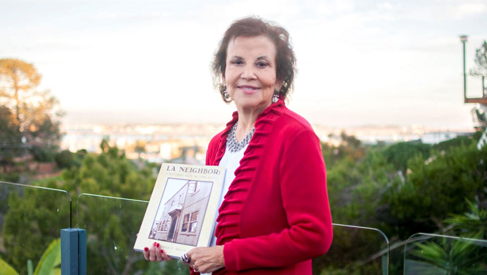 Maria Garcia holds her book La Neighborhood: A Settlement House in Logan Heights