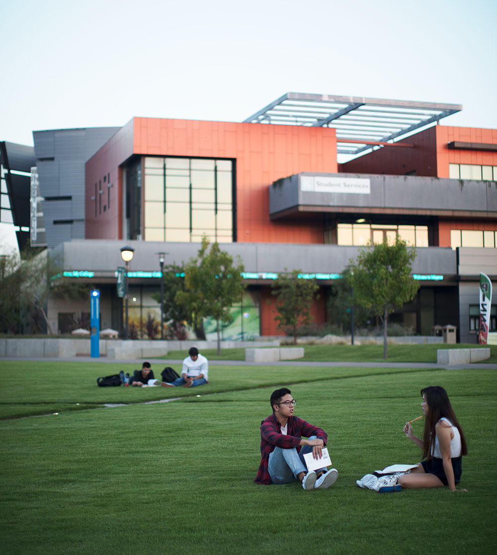 two students sit on the grass at miramar college