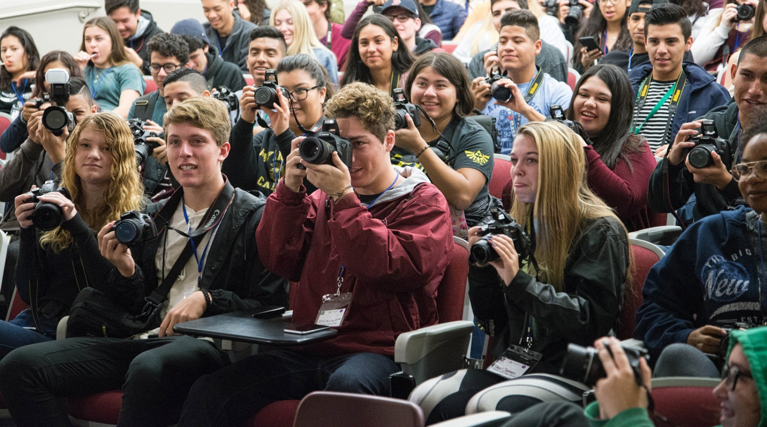 Students hold up their cameras to take a picture.