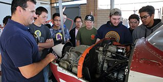 A group of students look at an engine