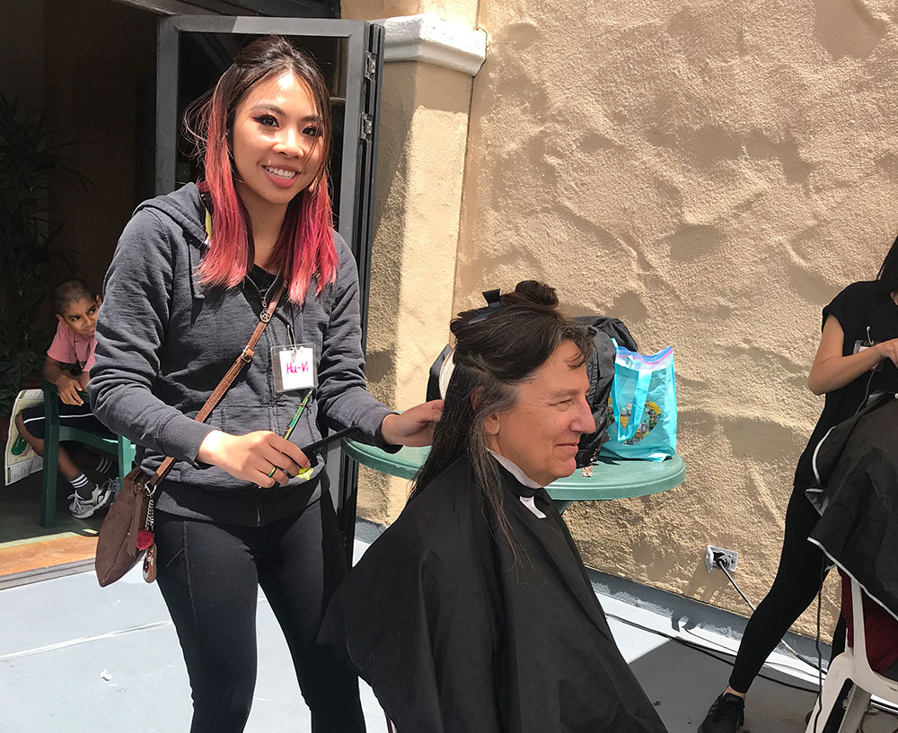 A cosmetology student gives a free haircut at the fair