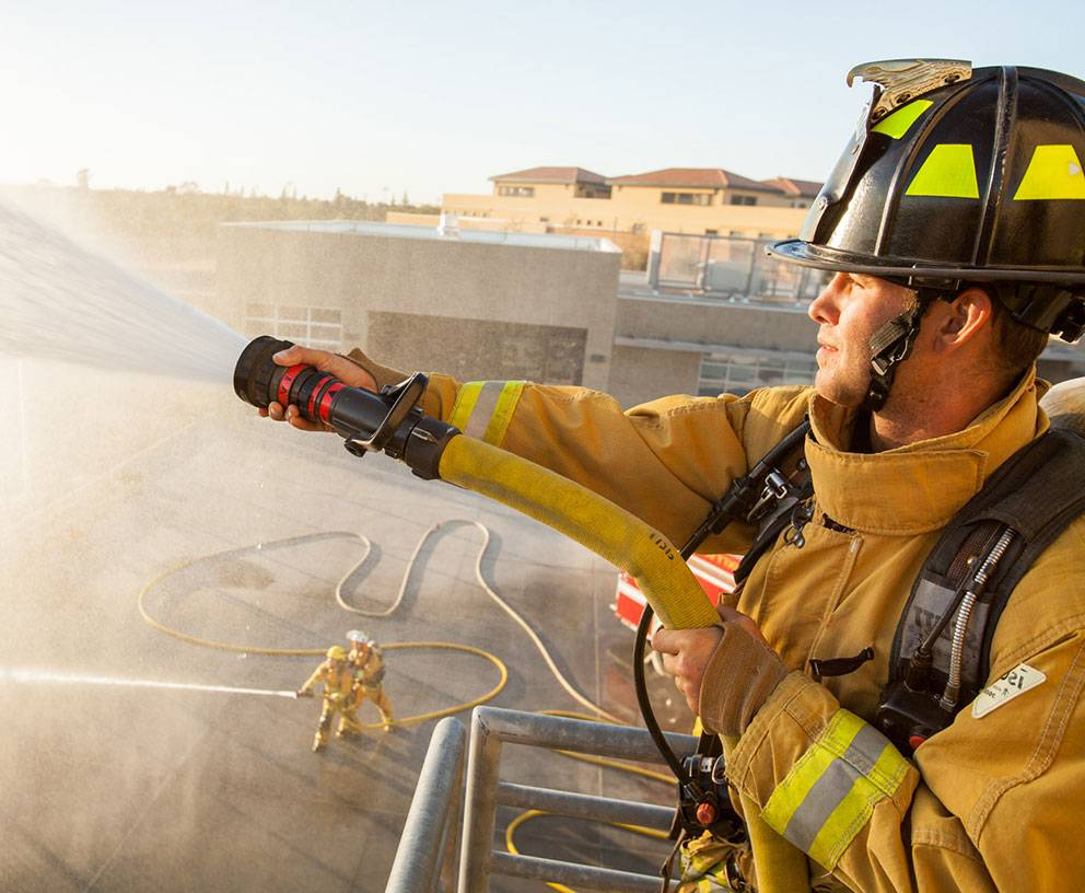 A fire trainee sprays a firehose
