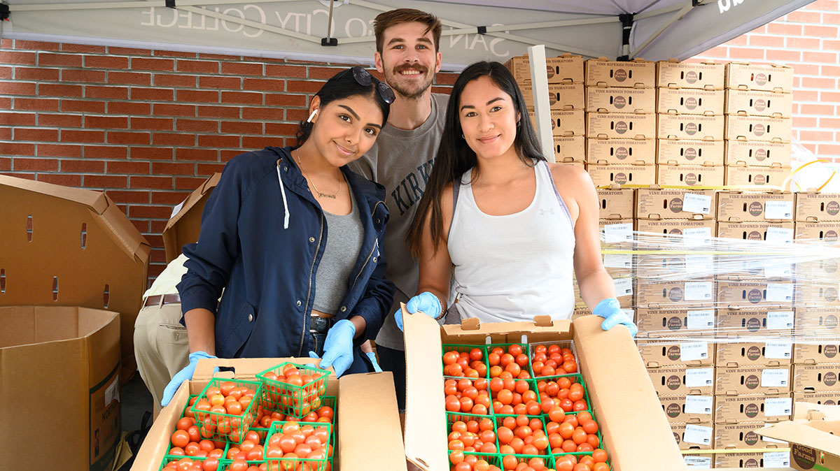 Volunteers hand out food during City College's farmers market
