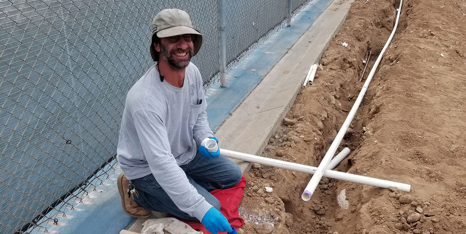 Irrigation technician Gerry Vanderpot works with pipes at mesa college