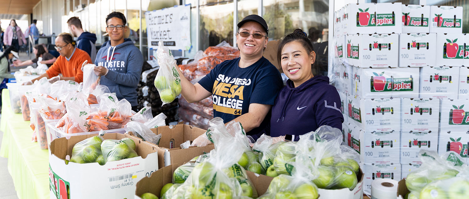 Volunteers hand out food during the Mesa College farmers market