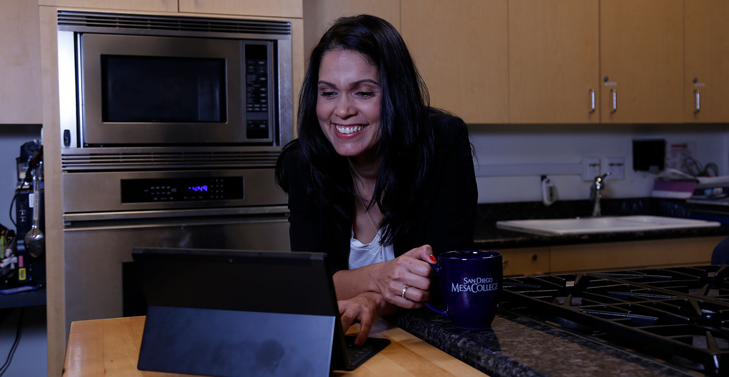 a student uses an a laptop in her kitchen