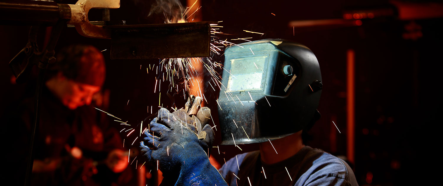A welding student protects themself from sparks with a mask
