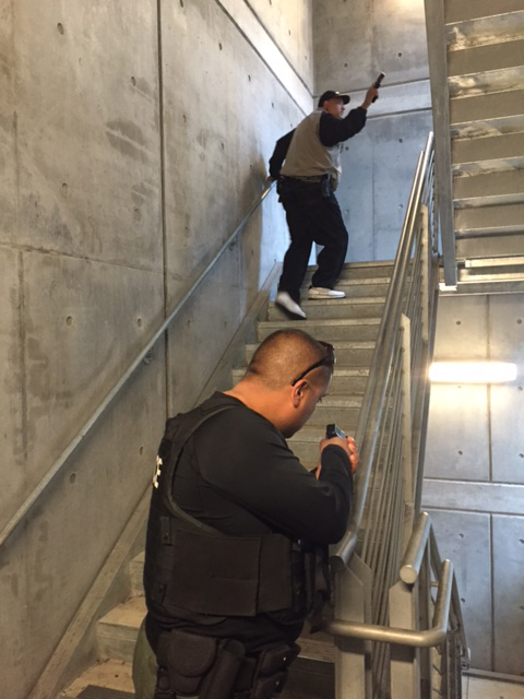 Two officers go up stairs with guns during a training exercise